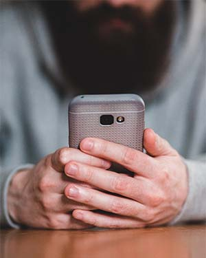 man using mobile phone to book a counselling session